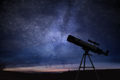 Silhouette of telescope and starry night sky in background. Astronomy and stars observing.