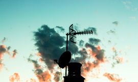 Silhouette of a television antenna and a chimney. With sky and clouds behind Royalty Free Stock Image