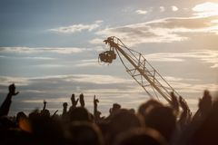 Silhouette of Television Camera hanging on crane is working on outdoor music festival Royalty Free Stock Images