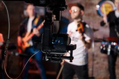 Silhouette of Television Camera hanging on crane working on stage and blurry concert background royalty free stock photo