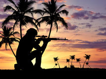 Silhouette of a terrorist. Concept of terrorism. Silhouette of a terrorist with a weapon against a background of a sunset with palm trees Royalty Free Stock Images