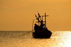 The Silhouette of Thai fisherman. With golden sky Stock Photography