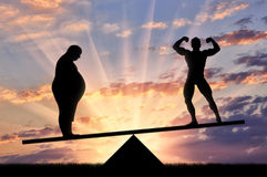 Silhouette thick and sports man on scales sunset Royalty Free Stock Photo
