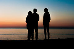 Silhouette of three friends at sunrise Royalty Free Stock Photo