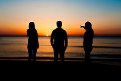 Silhouette of three friends at sunrise Stock Image