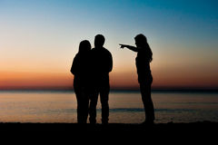 Silhouette of three friends at sunrise Stock Images