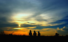 Silhouette of three girls sitting on grass at sunset. Silhouette of three girls sitting on grass at the time of sunset Stock Photos