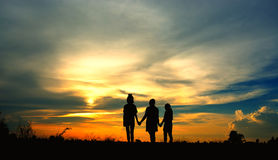 Silhouette of three girls standing holding hand with looking to the sun. Silhouette of girls standing on meadow and holding hand with looking to the sun Royalty Free Stock Images