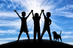 Silhouette of three happy children stock images