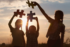 Silhouette of three happy children which playing on the field at stock images