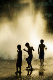 Silhouette of three kids playing in a fountain. Three young boys playing in outdoor fountain in Oregon, Portland Royalty Free Stock Photo