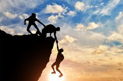 Silhouette of three male climbers rescuing another male climber pulling his arm stock images