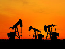 Silhouette three oil pumps. Three pumps over orange sky Royalty Free Stock Image