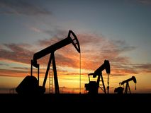 Silhouette three oil pumps. Three pumps over orange sky Stock Images