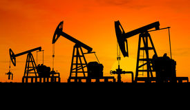 Silhouette three oil pumps. Three pumps over orange sky Royalty Free Stock Images