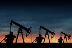 Silhouette of three oil pumps at sunset. Stock Image