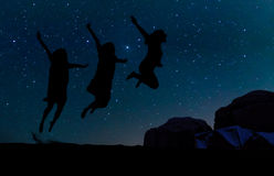 Silhouette of three people jumping on the sand hill, beneath the stars, Milky Way and stars over the mountain at Wadi Rum Royalty Free Stock Photography