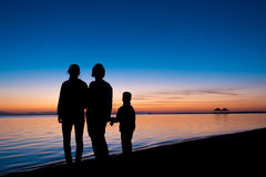 Silhouette of three people standing on the beach in sunrise Stock Photo