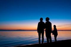 Silhouette of three people standing on the beach in sunrise. Vacation concept Royalty Free Stock Photography