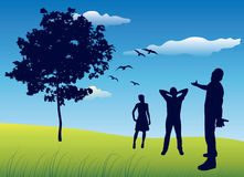 Silhouette of three people standing on summer field near tree, b Royalty Free Stock Photography