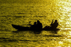 Silhouette of Three person kayaking Royalty Free Stock Photos