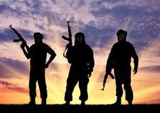 Silhouette of three terrorists Stock Photo