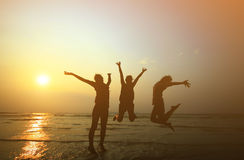 Silhouette of three young girls jumping with hands up royalty free stock photography