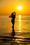 Silhouette to the beautiful girl at sunset Stock Photos