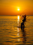 Silhouette to the beautiful girl at sunset royalty free stock photos