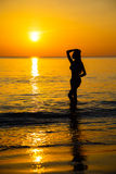 Silhouette to the beautiful girl at sunset Royalty Free Stock Images