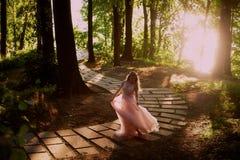 Silhouette tourbillonnant dans le coucher de soleil dans les beaux bois de la jeune mariée dans la robe de pêche avec la dentelle Photo libre de droits
