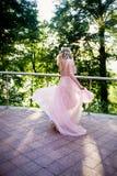 Silhouette tourbillonnant dans le coucher de soleil dans les beaux bois de la jeune mariée dans la robe de pêche avec la dentelle Photographie stock libre de droits