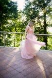 Silhouette tourbillonnant dans le coucher de soleil dans les beaux bois de la jeune mariée dans la robe de pêche avec la dentelle Image libre de droits