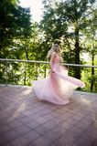 Silhouette tourbillonnant dans le coucher de soleil dans les beaux bois de la jeune mariée dans la robe de pêche avec la dentelle Images libres de droits