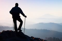 Silhouette of tourist with backpack and poles in hands stand on rocky view point and watching into morning landscape below. Royalty Free Stock Photo