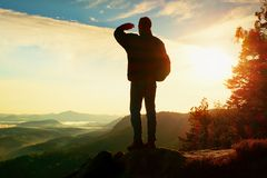 Silhouette of tourist with backpack. Sunny spring daybreak in rocky mountains. Hiker with sporty backpack stand on rocky view poin Stock Images