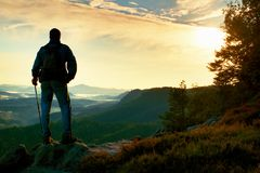 Silhouette of tourist with backpack. Sunny spring daybreak in rocky mountains. Hiker with sporty backpack stand on rocky view poin Stock Image