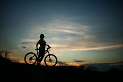 Silhouette of tourist and bike on sky background. Royalty Free Stock Photography