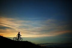 Silhouette of tourist and bike on sky background. Stock Photo