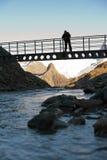 Silhouette of tourist on the bridge in mountains Royalty Free Stock Photo