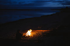 Silhouette of tourist girl around  campfire at night on the river shore. Stock Images