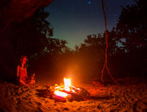 Silhouette of tourist girl around campfire at night on the river shore. Stock Image