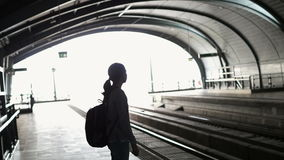 Silhouette tourist girl backpacker waiting for train at the open station, travel abstract stock video