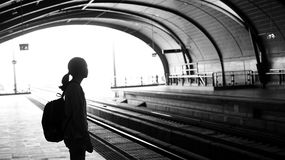 Silhouette for tourist girl backpacker waiting for train at the Royalty Free Stock Images