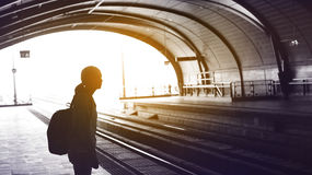 Silhouette for tourist girl backpacker waiting for train at the Royalty Free Stock Image