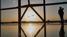 Silhouette of a tourist guy watching the take-off of the plane standing at the airport window at sunset in the evening. Travel concept, people in the airport stock footage