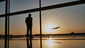 Silhouette of a tourist guy watching the take-off of the plane standing at the airport window at sunset in the evening. Travel concept, people in the airport stock video