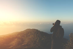 Silhouette tourist man shoot photo on peak of mountain with vint Royalty Free Stock Photography
