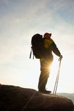 Silhouette of tourist with poles in hand. Hiker with big backpack stand on rocky view point above misty valley. Sunny spring daybr Stock Photo