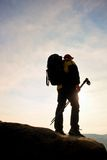 Silhouette of tourist with poles in hand. Hiker with big backpack stand on rocky view point above misty valley. Sunny spring daybr Royalty Free Stock Image